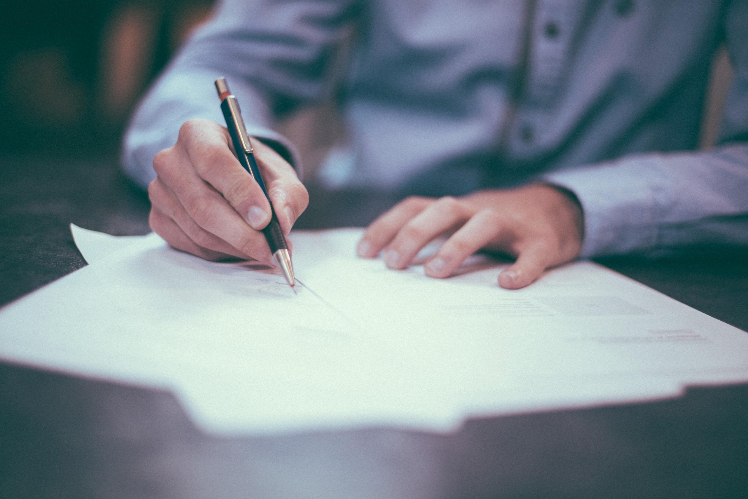 meżczyzna podpisuje dokumenty